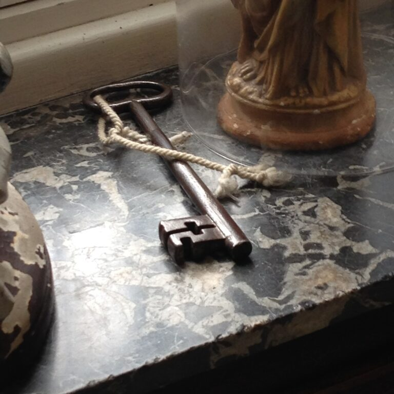 Old key on rope, on a window sill, next to a small statue of a saint under a glass dome