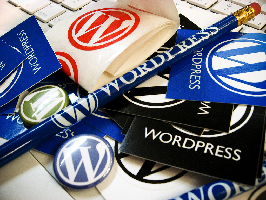pile of WordPress swag including pencils buttons and stickers