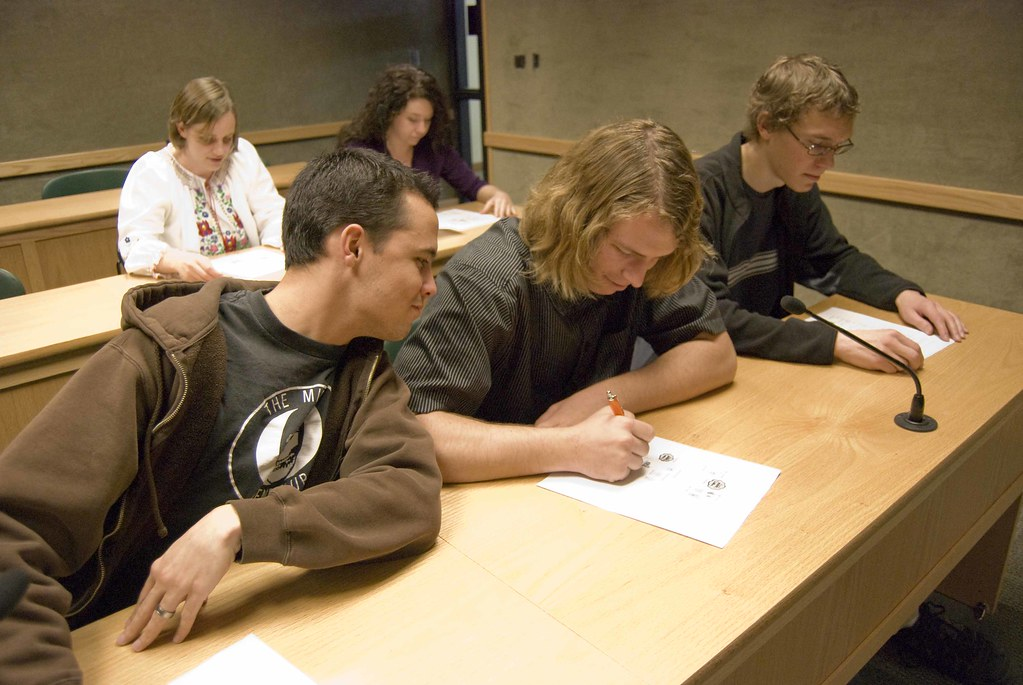 Classroom with two rows of desks, three male students in the front row, one leans over to read what's on the paper of his neighbor. Two female students in the back.